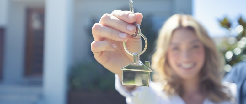 home-loan-borrower-holding-up-keys-in-front-of-house