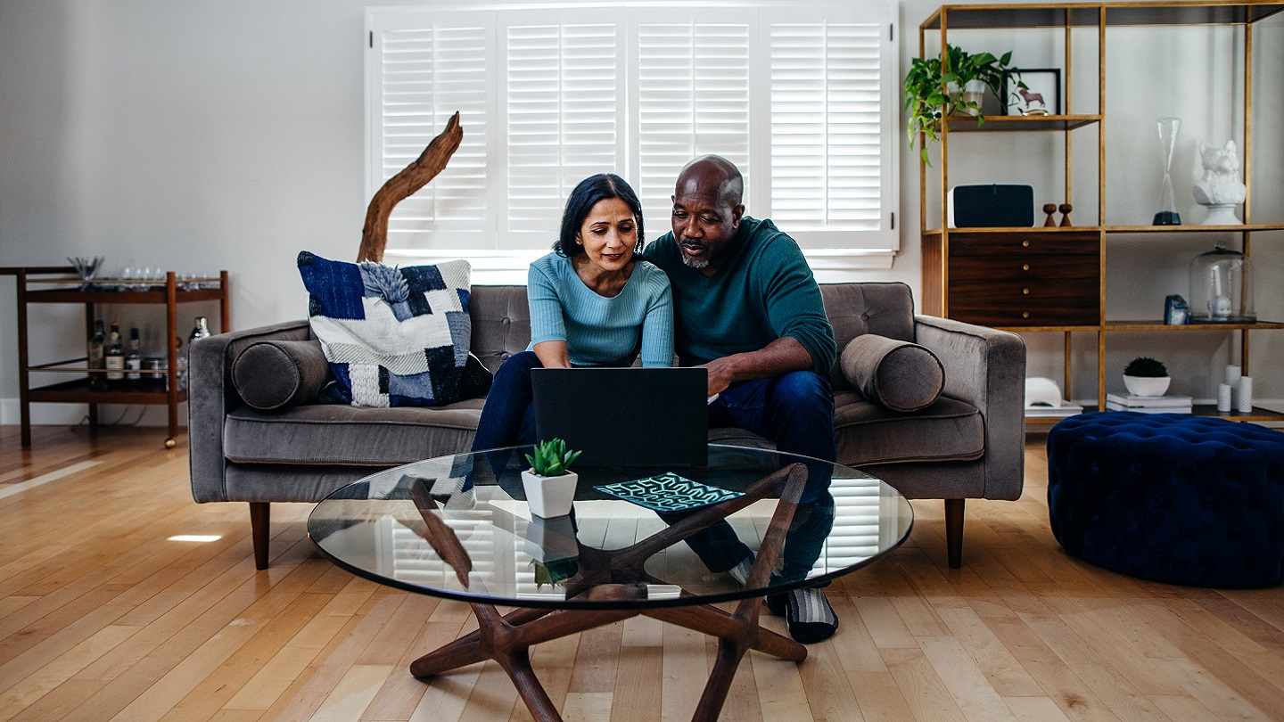 couple on sofa checking their savings account balance on a laptop