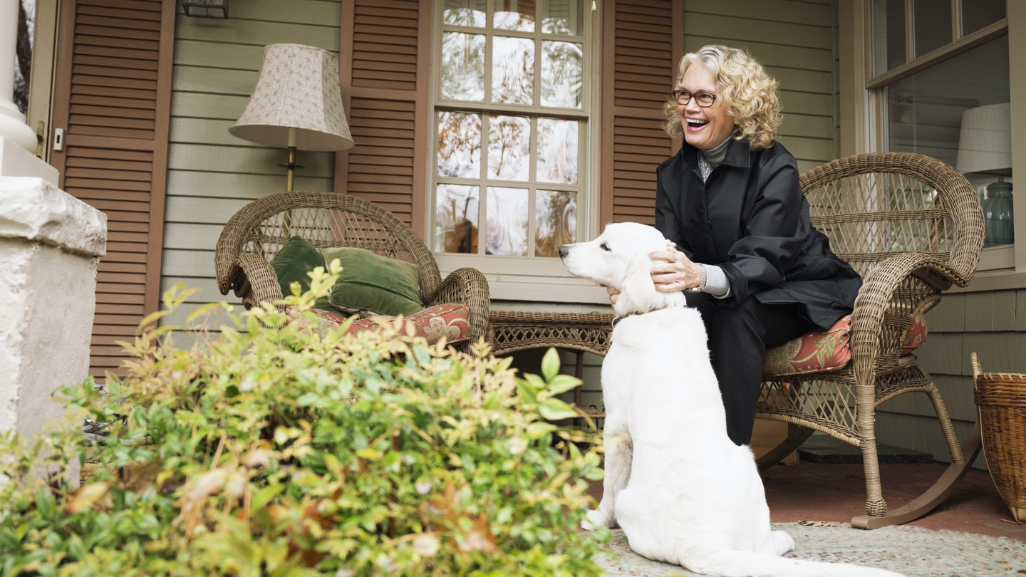 Woman in 50s, sitting on porch with dog, in front of the home she just bought.