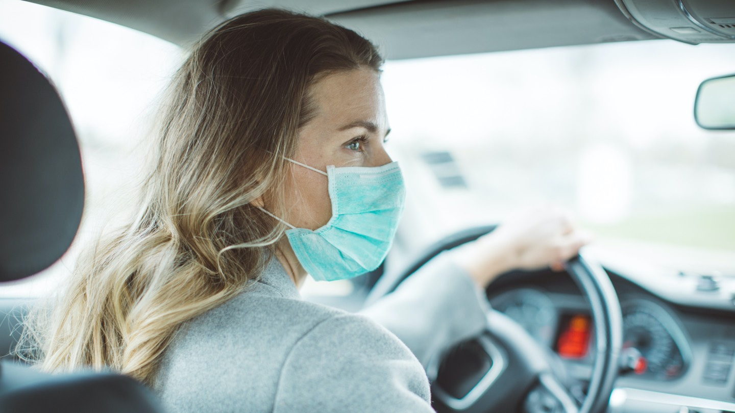 Blonde woman sitting behind steering wheel with face mask on.