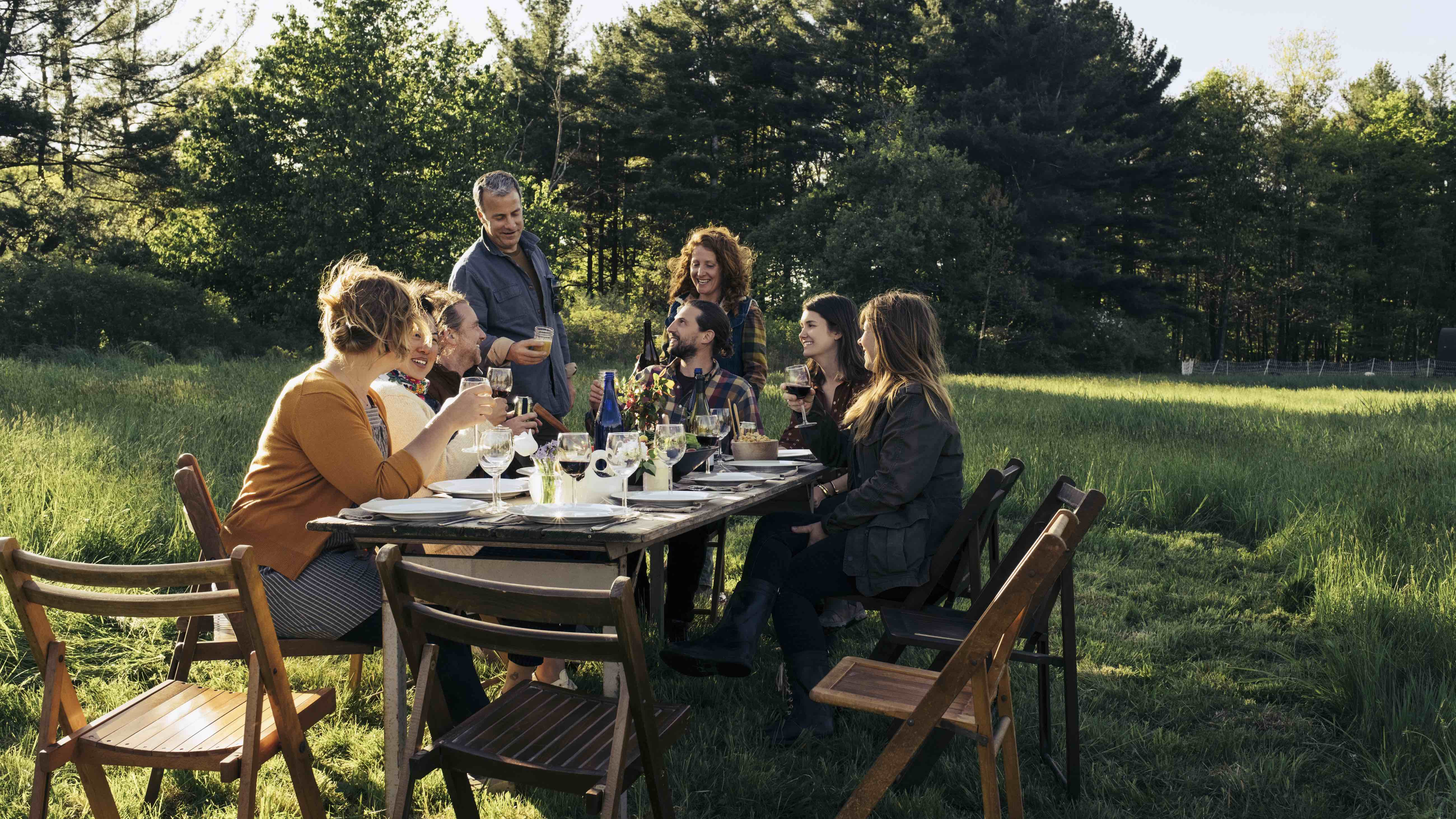 Group with ethical investments eating in a field